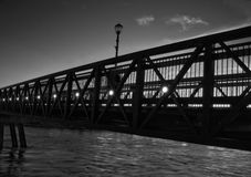 A steel bridge with lamp post in black and white. With small clouds Stock Photos