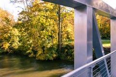 Steel bridge over autumn river. Silver colored bridge over bright autumn river Stock Photo