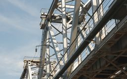 Steel bridge over blue sky with clouds in sunny day. Metal indus Royalty Free Stock Photo
