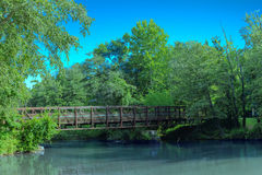 Steel Bridge Over Murky River. In forest Stock Photo