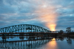 Steel bridge over the river. The light piercing through the clouds Stock Image