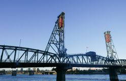 Steel Bridge, Portland Oregon. Two bridges spanning the Willamette river in Portland Oregon with cityscape in background with blue sky, water, pedestrians,  and Royalty Free Stock Images