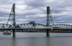 Steel bridge spanning the Columbia River. Steel bridge with arches spanning the Columbia river with flag and boat and cityscape in background Stock Photo