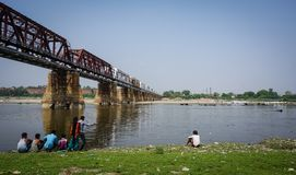 Steel bridge at sunny day in Agra, India. Agra, India - Jul 13, 2015. Steel bridge with Yamuna River at sunny day in Agra, India. Agra is a city on the banks of Stock Image