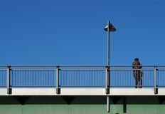 Steel bridge under a blue sky with woman leaning against the railing rear view and street lamp stock image