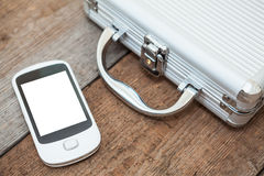 Steel briefcase with mobile phone laying on floor Stock Photos