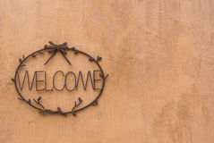 Steel cast welcome sign on earth tone cement wall. Steel cast welcome sign on earth tone rough textured cement wall Stock Photography