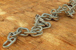 Steel chain background. Heavy steel chain on an old wooden surface background 3d illustration stock illustration
