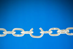 Steel chain with a broken link. Over blue background royalty free stock photo