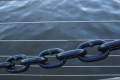 Steel chain. In front of wire balustrading with water background Stock Photos