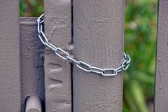 Steel chain hanging on a gray iron gate Stock Photography