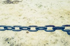 Steel chain on a sandy background - restriction, freedom, justice and security concept. Close-up view of a steel chain running across a sandy background with royalty free stock images