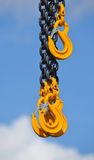 Steel Chain with three yellow hooks. With sky and clouds in background Stock Photos