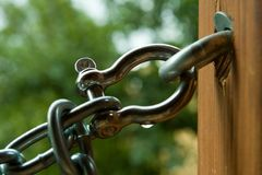 Steel chain and wooden beam. Steel chain attached to a wooden beam Royalty Free Stock Images