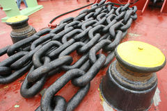 Steel chains. Old red marine deck with chains and bollards royalty free stock photo