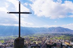 A steel Christian cross on top of a mountain and a city landscape. Beautiful cityscape. Italy stock image