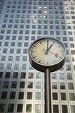 Steel clock and Canary Wharf tower. A Steel Clock face showing the time of 1 o clock. The image is in portrait composition with space for copy royalty free stock photo