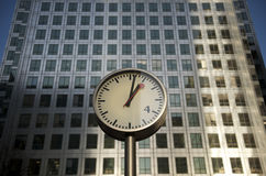 Steel clock and Canary Wharf tower. A Steel Clock face showing the time of 1 o clock. The Steel and Glass structure of the Canary Wharf office block in London's stock photo