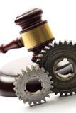 Steel cogwheels on judge's wooden gavel Stock Photo