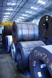 Steel Coils Warehouse. Warehouse with Stacked up steel coils (Hot Rolled / HR and Cold Rolled CR) of virgin grade. The coils are slitted and used for Royalty Free Stock Images