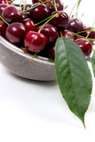 Steel colander with red sweet cherry  on a white backgro Royalty Free Stock Images