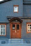 Steel colored wooden house facade with brown closed door and win Stock Image