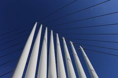 Steel columns and cables of modern bridge looking up blue sky royalty free stock image