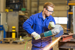 Steel construction worker cutting metal with angle grinder Royalty Free Stock Photo