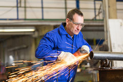 Steel construction worker grinding metal with angle grinder Stock Photo
