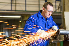 Steel construction worker grinding metal with angle grinder. Steel construction worker grinding metal with an angle grinder Royalty Free Stock Photography