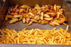 Steel container with roasted potato wedges, french fries Royalty Free Stock Photography
