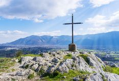 A steel cross on top of the mountain with rays of the sun on a blue skies. Stock image. royalty free stock photography