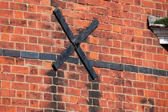 Steel cross used to support brick wall. Stock Images