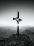 Steel crucifix at mountain peak in Alps. Sharp rocky summit, daybreak Sun in sky. Royalty Free Stock Images