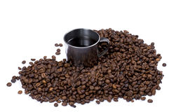 The steel cup of coffee surrounded with coffee grains Stock Photo