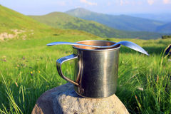 Steel cup and spoon. On outdoor background Stock Images