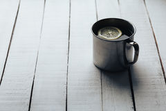Steel cup of tea with a slice of lemon on a white vintage wooden background. Royalty Free Stock Image