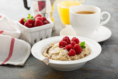 Steel cut oatmeal porridge with raspberry and coconut. Flakes for breakfast Stock Photos