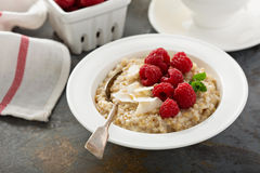 Steel cut oatmeal porridge with raspberry and coconut. Flakes for breakfast Royalty Free Stock Photography