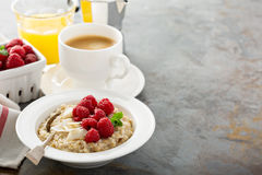 Steel cut oatmeal porridge with raspberry and coconut. Flakes for breakfast with copyspace Stock Photos