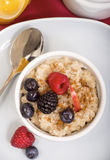 Steel cut oatmeal served with fresh fruit. Delicious bowl of freshly made steal cut oatmeal served with fresh blackberries, blueberries, raspberries and apple Stock Photo