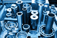Steel cylinders, pistons and tools in workshop. Industry theme. Stock Image