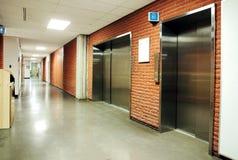 Steel door elevators in deserted hallway. Freight and regular steel door elevators with signs in an empty hallway of modern building. Can be office, school Stock Photography