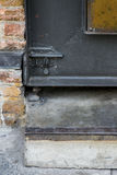 The steel door latch on black rustic steel door beside bare bric Stock Photo