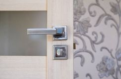 Steel door, wood trim. Several locks and a handle royalty free stock image