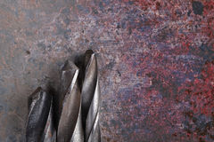 Steel drill bits on rusty iron background Stock Photos