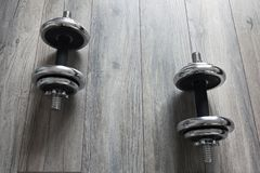 Background with dumbbells on a wooden floor. Steel dumbbells on the wooden floor royalty free stock image