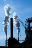 Steel factory with chimneys and white smoke Stock Images