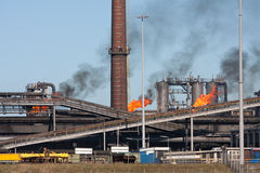 Steel factory with smokestack and gas flaring Stock Image