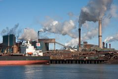 Steel factory with smokestacks and cargo ship Stock Image